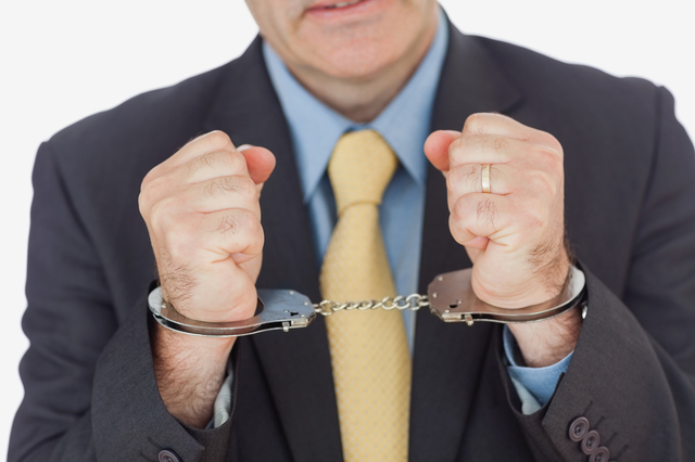 Close-up of businessman with handcuffed hands over white background